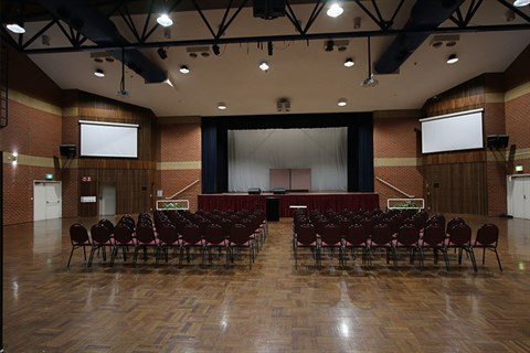 Interior shot of Bicentennial Hall looking towards the stage with seats arranged in theatre style