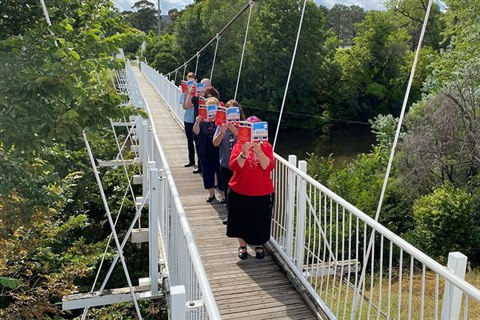 Library staff reading on Queanbeyan suspension bridge